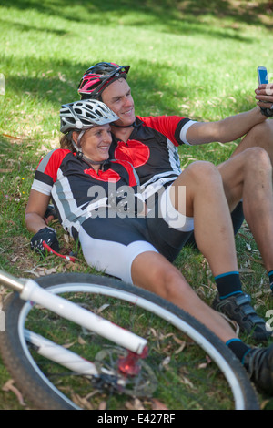 Cyclists on grass taking selfie - Stock Photo