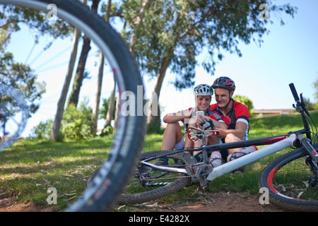 Cyclists on grass using smartphone - Stock Photo