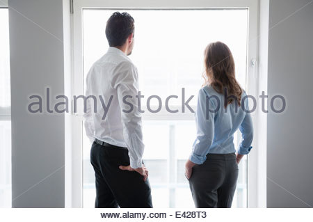 Businessman and woman looking out of window - Stock Photo