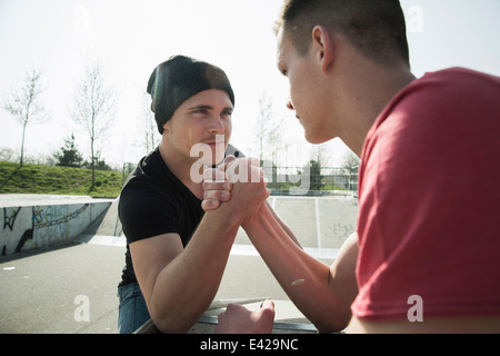 Young men arm-wrestling in skatepark - Stock Photo