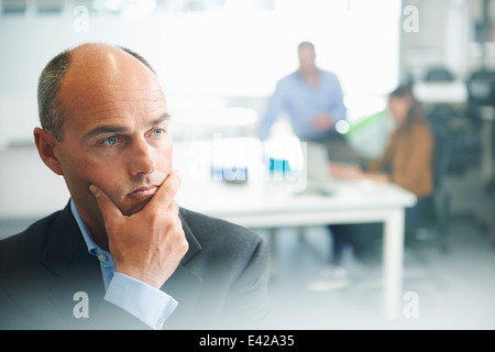 Man thinking, people in background - Stock Photo