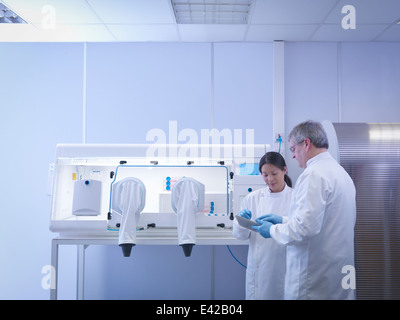 Scientists discussing notes in lab next to laboratory workstation - Stock Photo