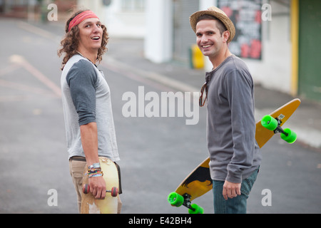 Portrait of two male adult friends with skateboards on city street - Stock Photo