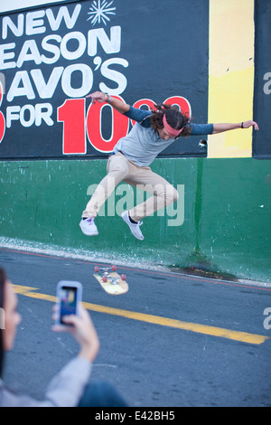 Young adult male being photographed on smartphone doing skateboarding trick - Stock Photo