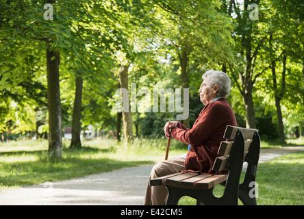 Senior woman sitting on park bench - Stock Photo