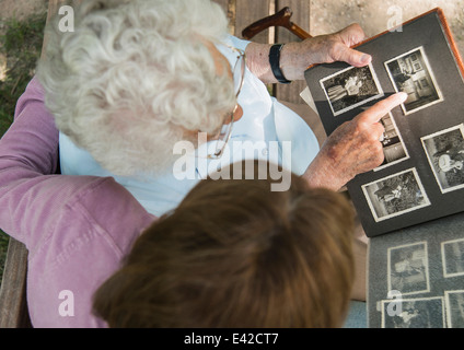 Senior woman sitting on park bench with granddaughter, looking at old photograph album - Stock Photo