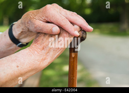 Senior woman's hands, holding walking stick - Stock Photo