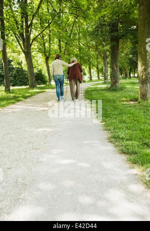 Senior woman and granddaughter walking through park, using walking stick - Stock Photo