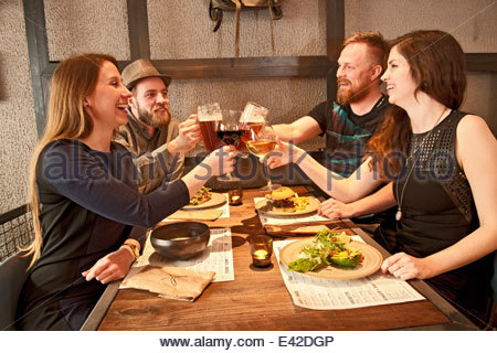 Friends toasting at hipster bar - Stock Photo