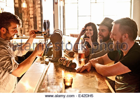 Friends drinking beer at hipster bar - Stock Photo
