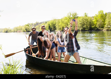 Group of friends in a row boat taking photo of themselves - Stock Photo