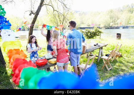 Group of friends setting up picnic - Stock Photo