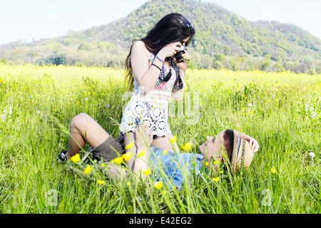 Young couple in field, woman photographing man - Stock Photo