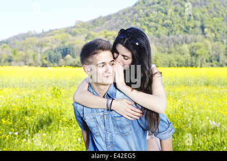 Young couple in field, man giving woman piggy back - Stock Photo