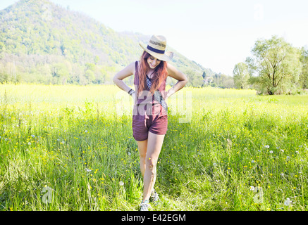 Young woman standing in field - Stock Photo
