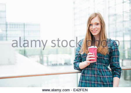 Portrait of young woman in city with takeaway coffee - Stock Photo