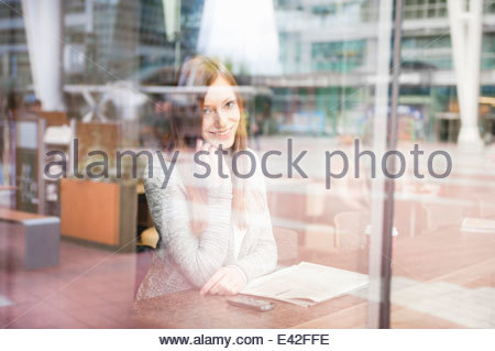Young woman looking out of cafe window chatting on smartphone - Stock Photo