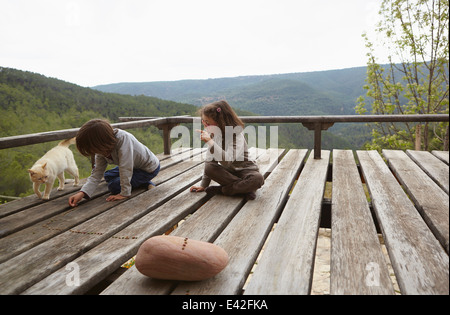 Young brother and sister playing on rural balcony - Stock Photo