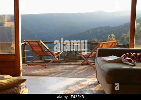 View from sitting room onto sunlit rural balcony - Stock Photo
