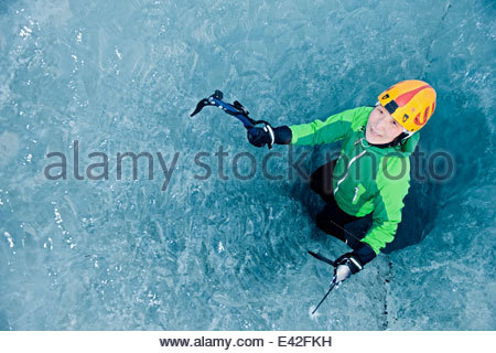 Female ice climber climbing out of pothole in glacier, Svinafellsjokull, Vatnajokull National Park, Iceland - Stock Photo