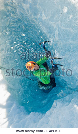 Mature female ice climber climbing out of pothole in glacier, Svinafellsjokull, Vatnajokull National Park, Iceland - Stock Photo