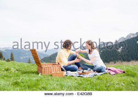 Mid adult couple having picnic, Wallberg, Tegernsee, Bavaria, Germany - Stock Photo