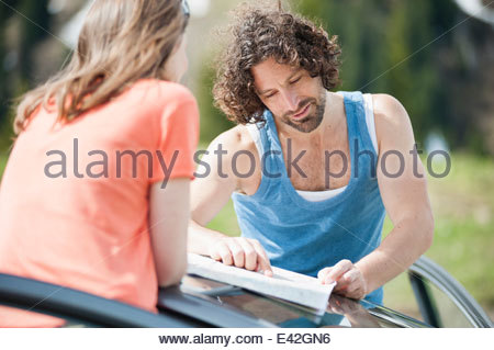 Mid adult couple looking at map on car roof - Stock Photo