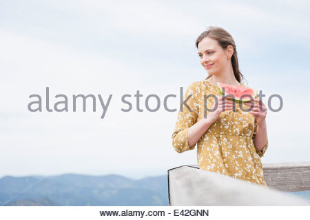Mid adult woman eating watermelon, Wallberg, Tegernsee, Bavaria, Germany - Stock Photo