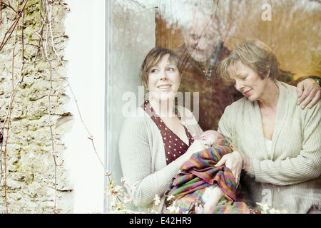 Mother with baby and grandparents looking out of window - Stock Photo