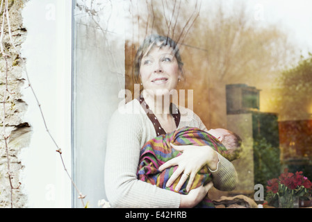 Mother with baby looking out of window - Stock Photo
