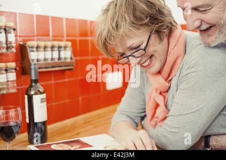 Couple reading cook book in kitchen - Stock Photo