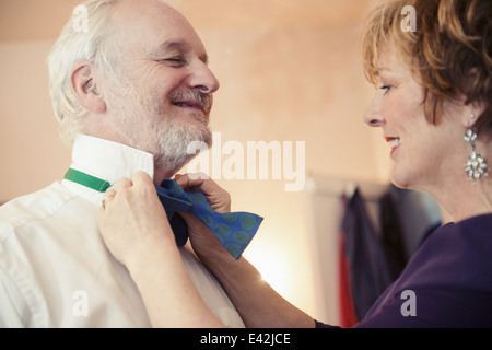 Mature woman putting bow tie on senior man - Stock Photo