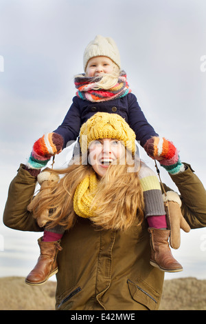 Smiling mid adult woman carrying daughter on shoulders at coast - Stock Photo