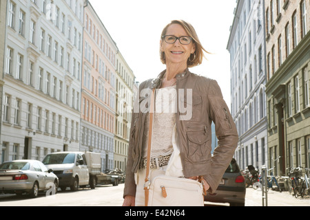 Portrait of senior woman shopping in the city - Stock Photo