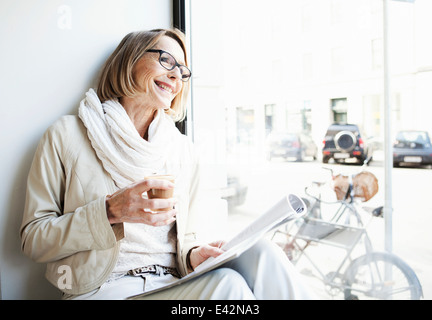 Senior woman having a coffee in cafe window seat - Stock Photo