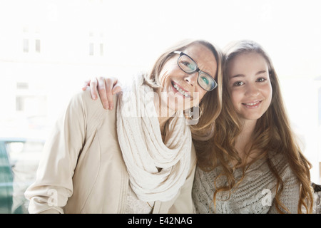 Portrait of teenage girl and grandmother in cafe window seat - Stock Photo