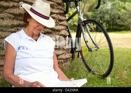 Senior woman leaning against palm tree reading in park - Stock Photo