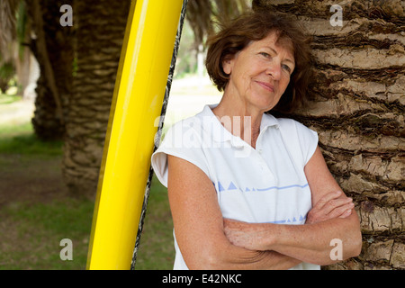 Portrait of senior woman leaning against palm tree in park - Stock Photo