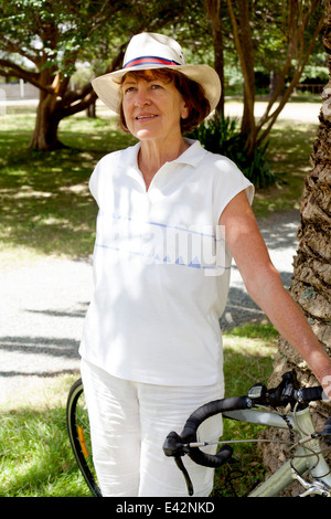 Portrait of senior woman and with bicycle in park - Stock Photo