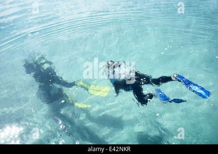 Underwater view of male teacher and boy scuba diving in sea - Stock Photo