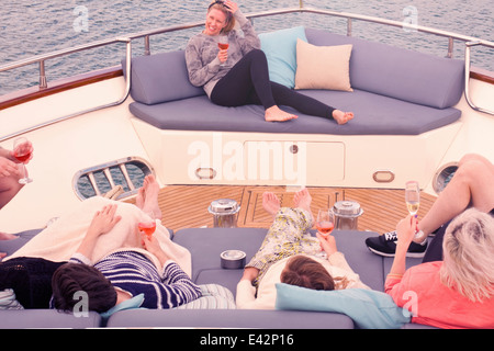 Group of adult friends enjoying a relaxing drink on board yacht - Stock Photo