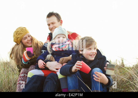 Smiling mid adult couple with two children at coast - Stock Photo