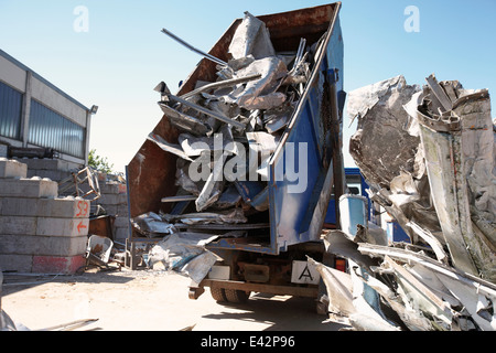 Dump truck emptying aluminium from skip into scrap yard - Stock Photo