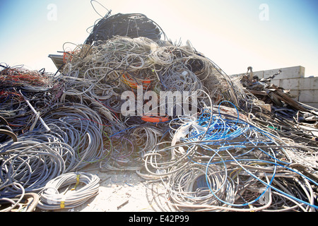 Heap of coiled and tangled cables in scrap metal yard - Stock Photo