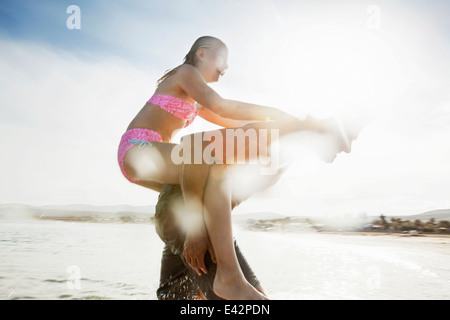 Father giving daughter piggy back on beach - Stock Photo