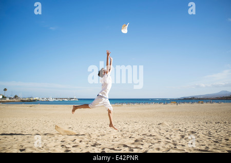 Boy jumping and throwing hat mid air on beach - Stock Photo
