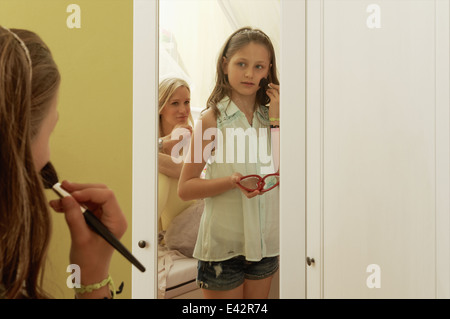 Girl putting on blusher in mirror whilst mother watches - Stock Photo