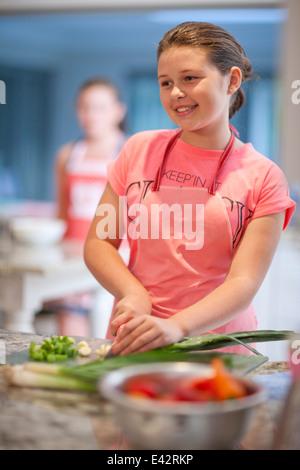 Teenage girl preparing leeks in kitchen - Stock Photo