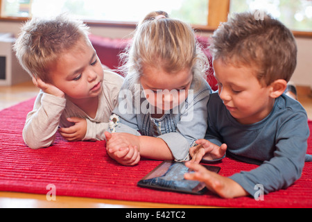 Two boys and a girl using digital tablet at nursery school - Stock Photo