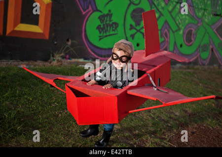 Boy wearing flying goggles running in toy airplane in park at night - Stock Photo